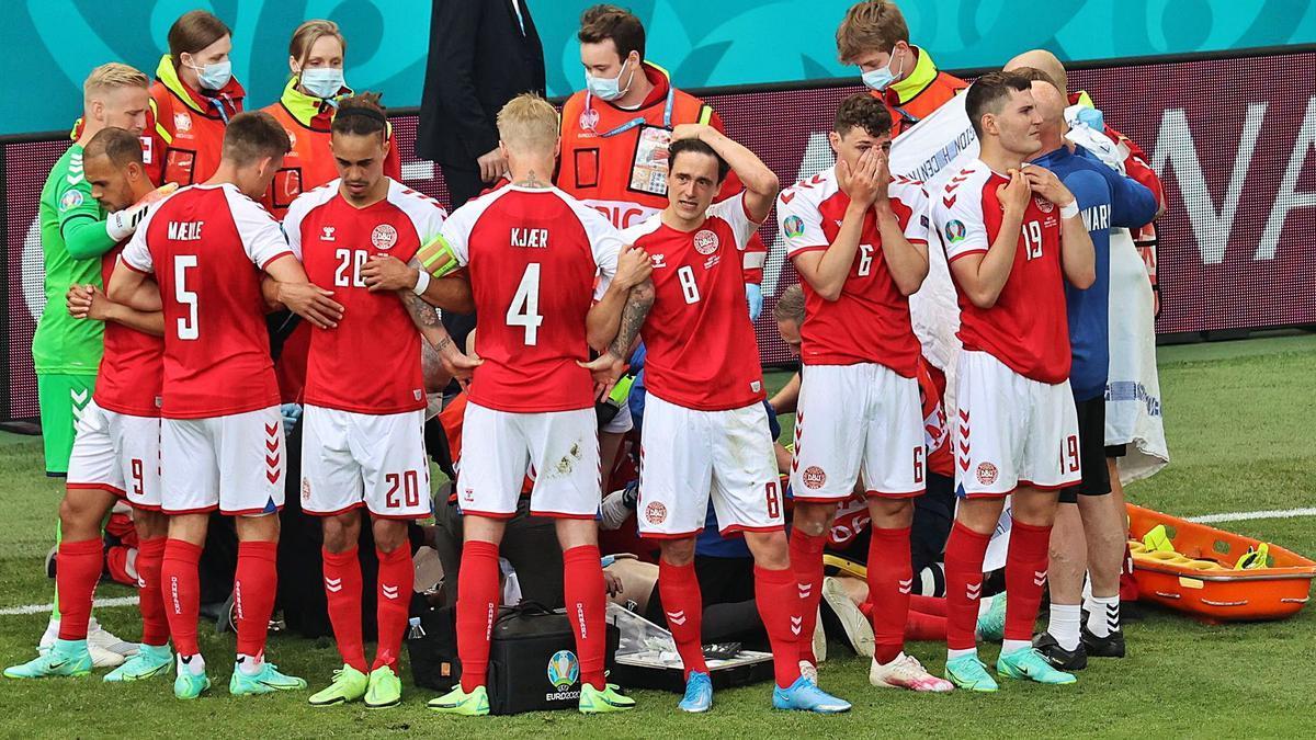 Los jugadores daneses, consternados, forman una barrera para que las cámaras no grabasen a su compañero tendido en el suelo. |  // EFE