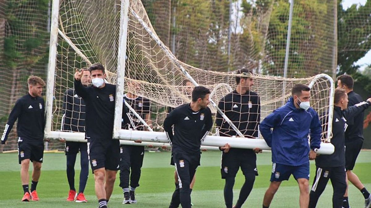 Los jugadores del Cartagena transportan una portería en el entrenamiento de ayer.