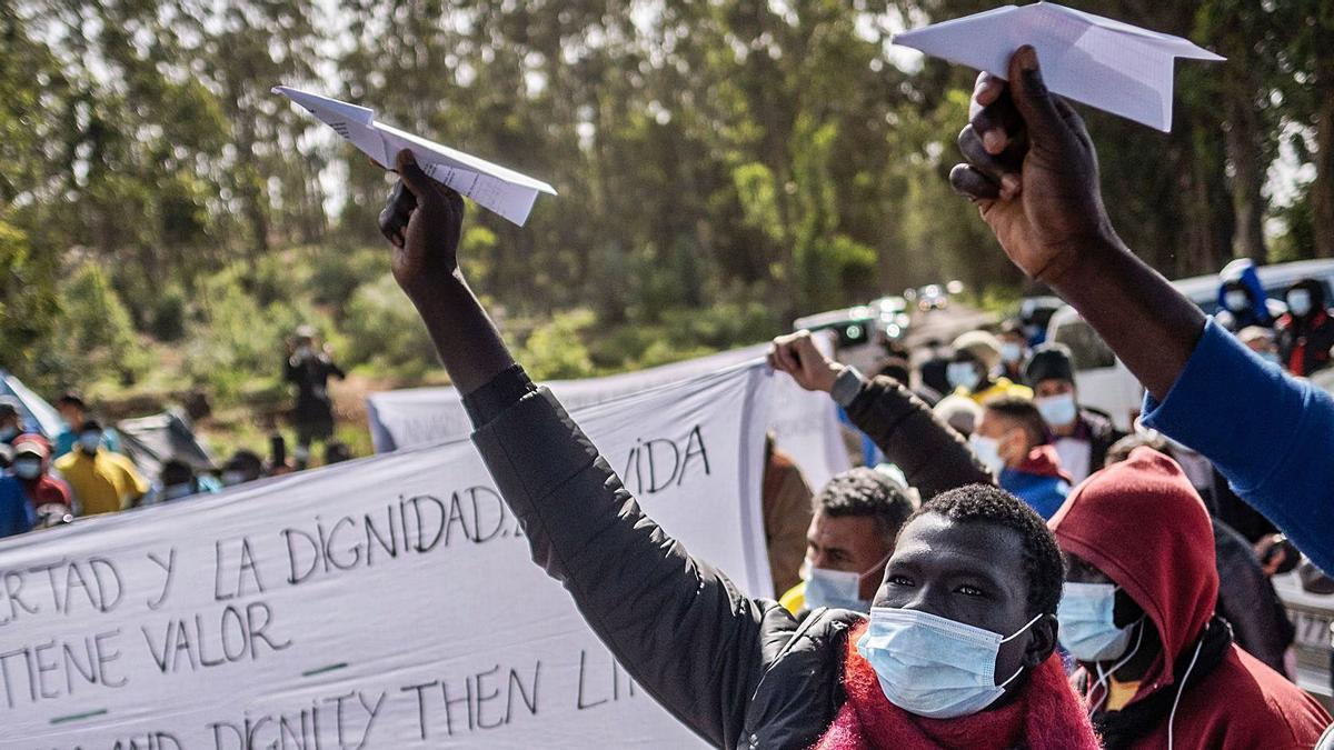 Imágenes de inmigrantes que se manifestaron el sábado en las puertas del campamento de La Raíces, en La Laguna, reclamando que se les deje continuar sus viajes hacia el continente.     LP/DLP