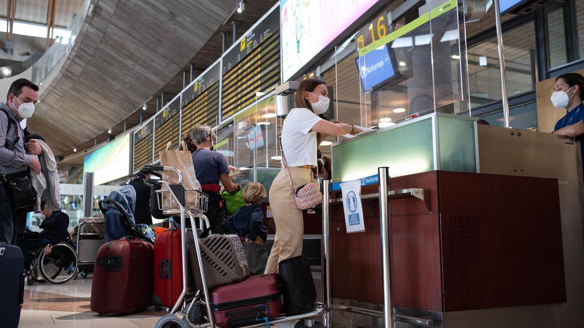 Una pasajera entrega documentación en un mostrador de facturación.