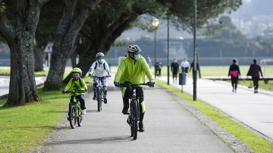 Una familia pasea en bicicleta y con mascarillas.