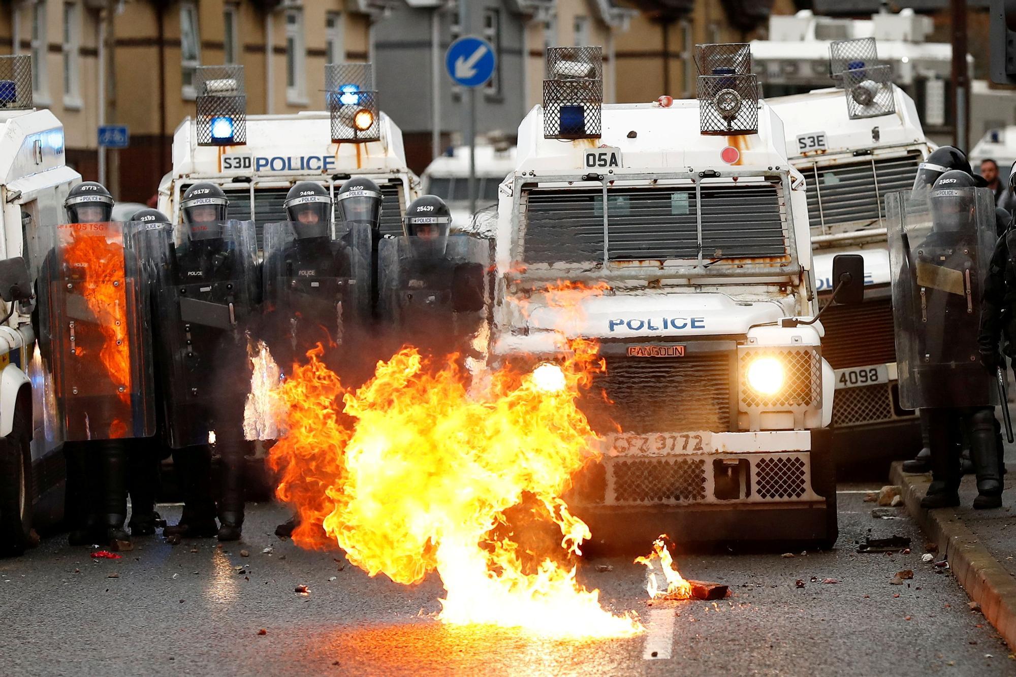 Un incendio arde frente a la policía en Springfield Road mientras continúan las protestas en Belfast. Reuters
