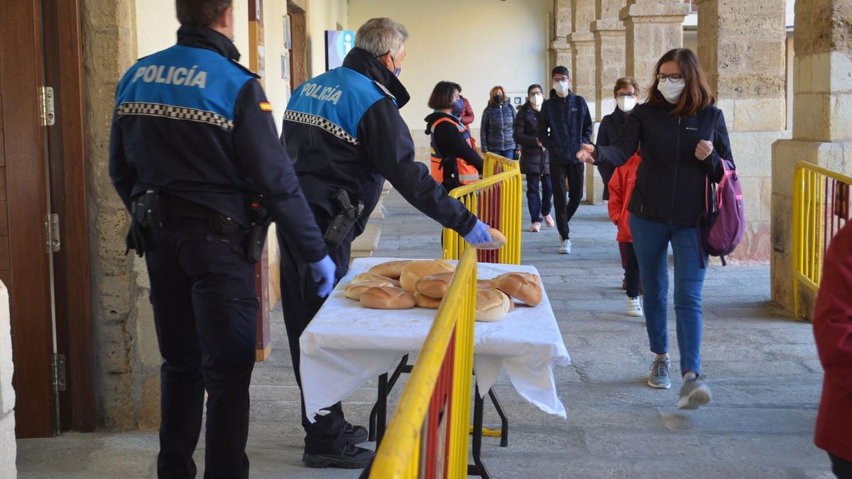 Varios vecinos guardan cola para recoger el tradicional pan de la Veguilla. / E. P.