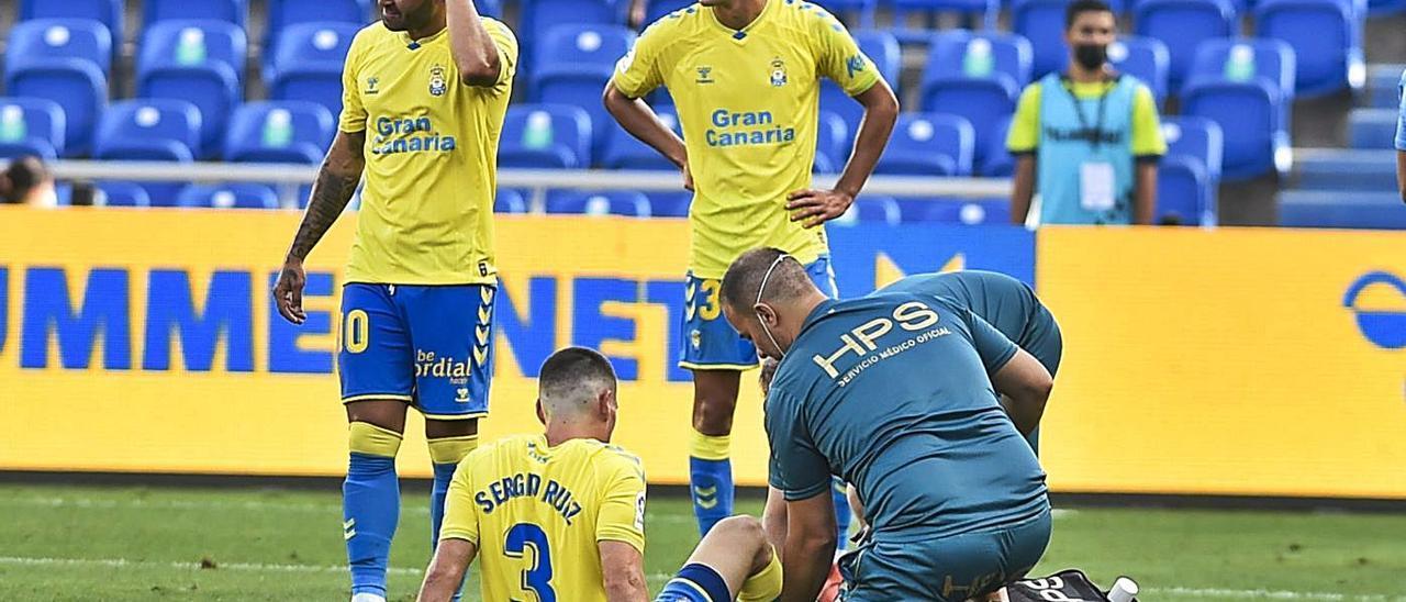 Sergio Ruiz, atendido por el 'fisio' Juan Naranjo ante la presencia de Jesé y Cardona, el sábado pasado.     ANDRÉS CRUZ