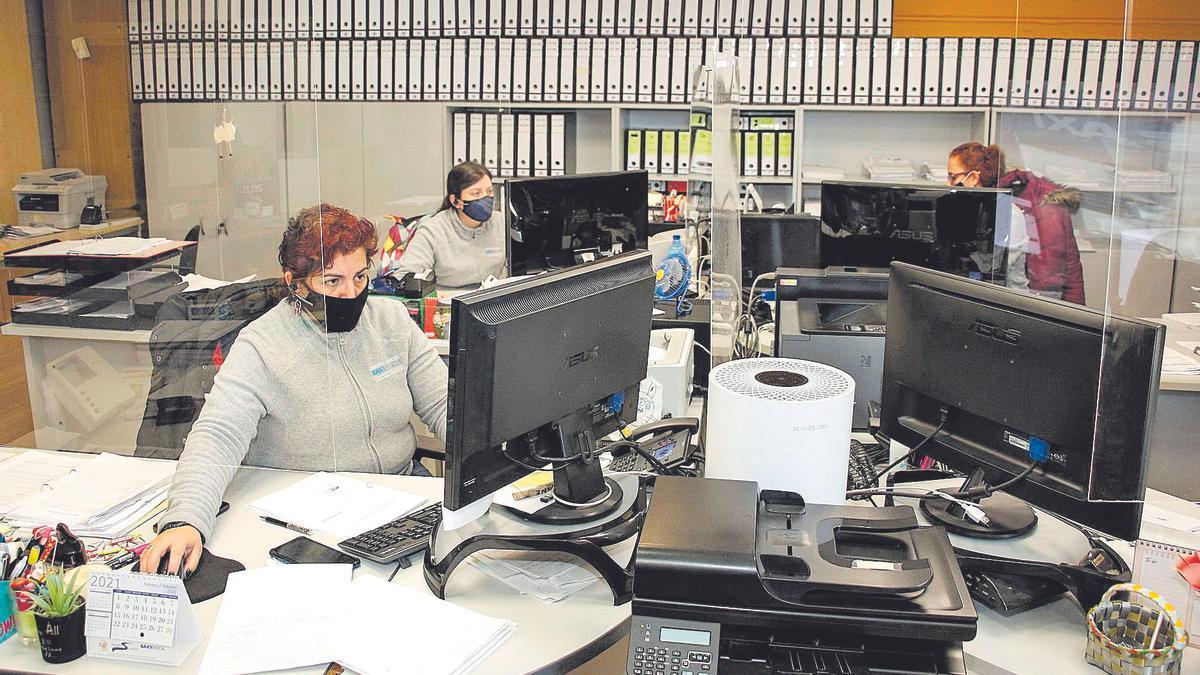Oficina del servicio de atención de Tecno Servicio Avilés y detalle de un repartidor de costes y llave termostática de un radiador. | Pablo Solares