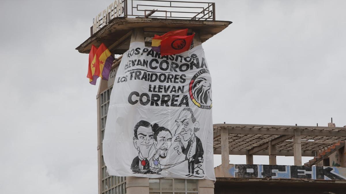Banderas y pancarta colocada en lo alto de la nave abandonada