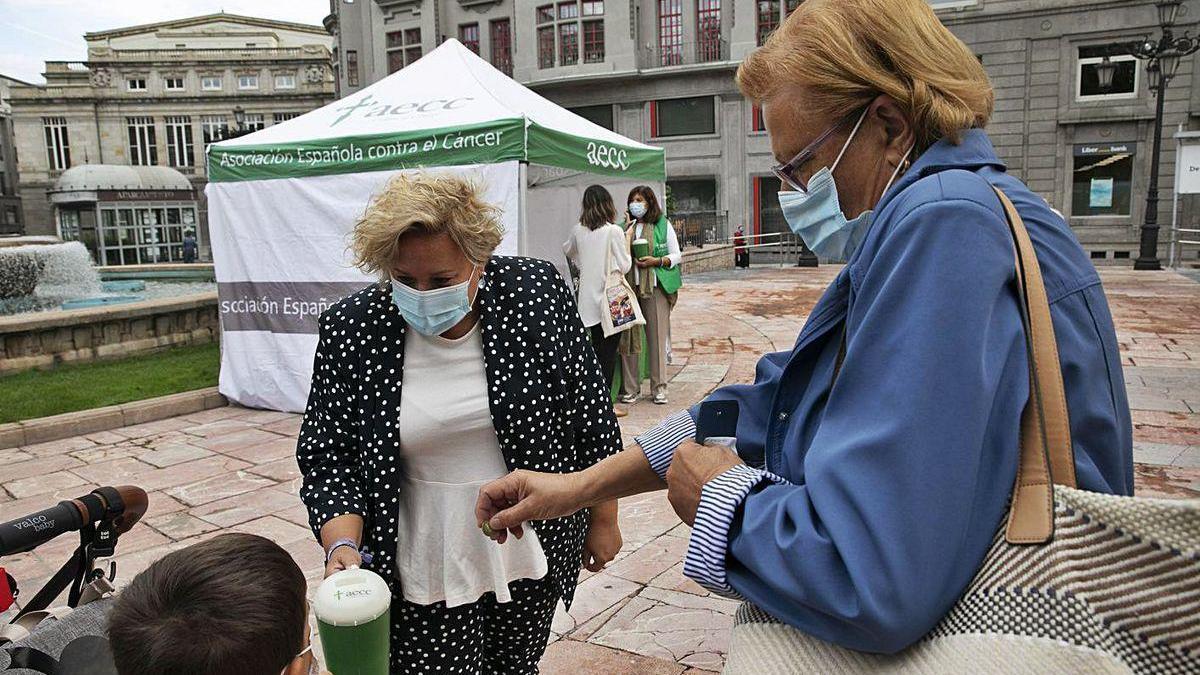 La voluntaria Isabel Garrido recibe el donativo de una familia.