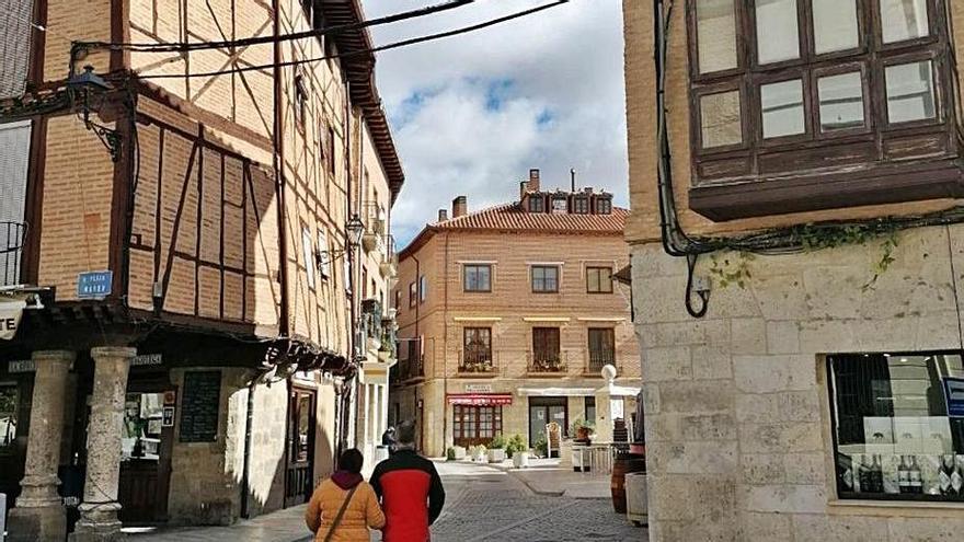 Vecinos pasean por una calle de Toro con cableado en fachadas. | M. J. C.