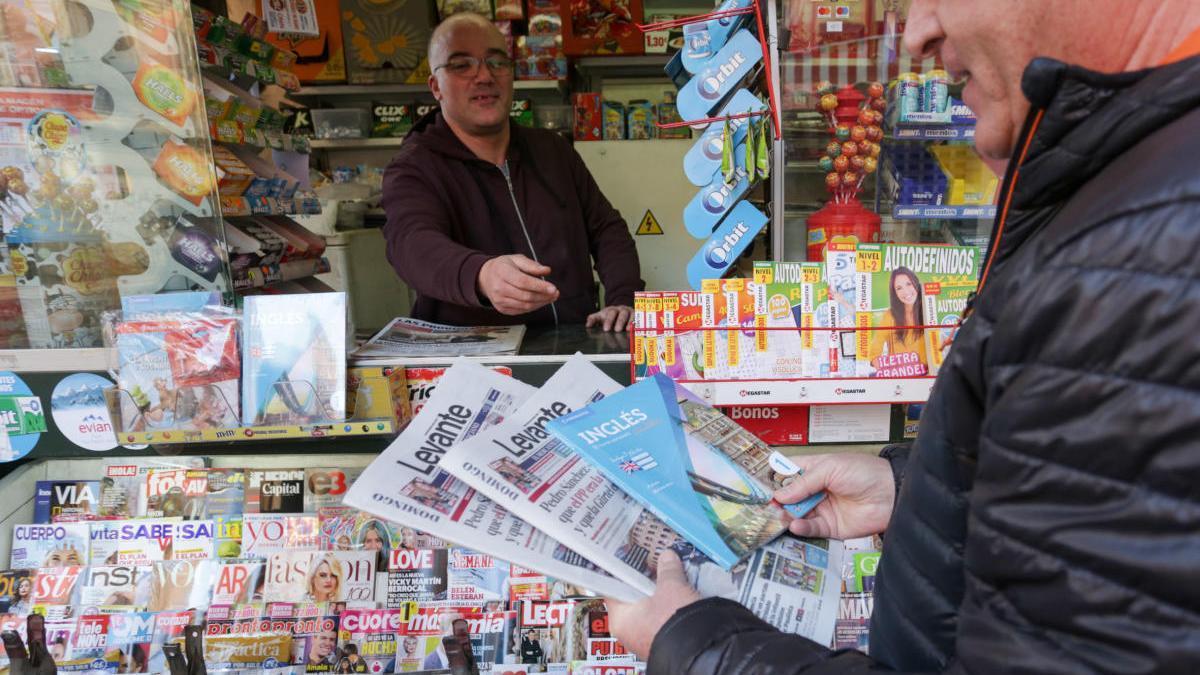 Una persona compra el periódico en Valencia.