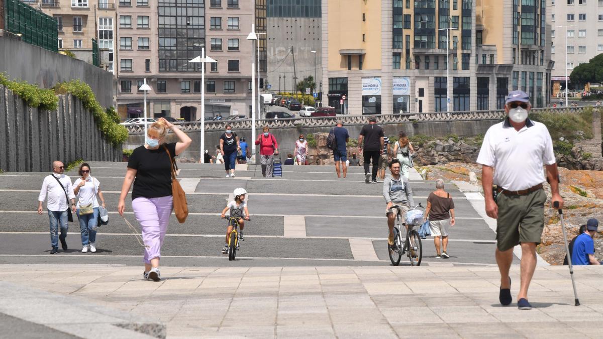 Ciudadanos con mascarilla en el paseo marítimo de A Coruña.