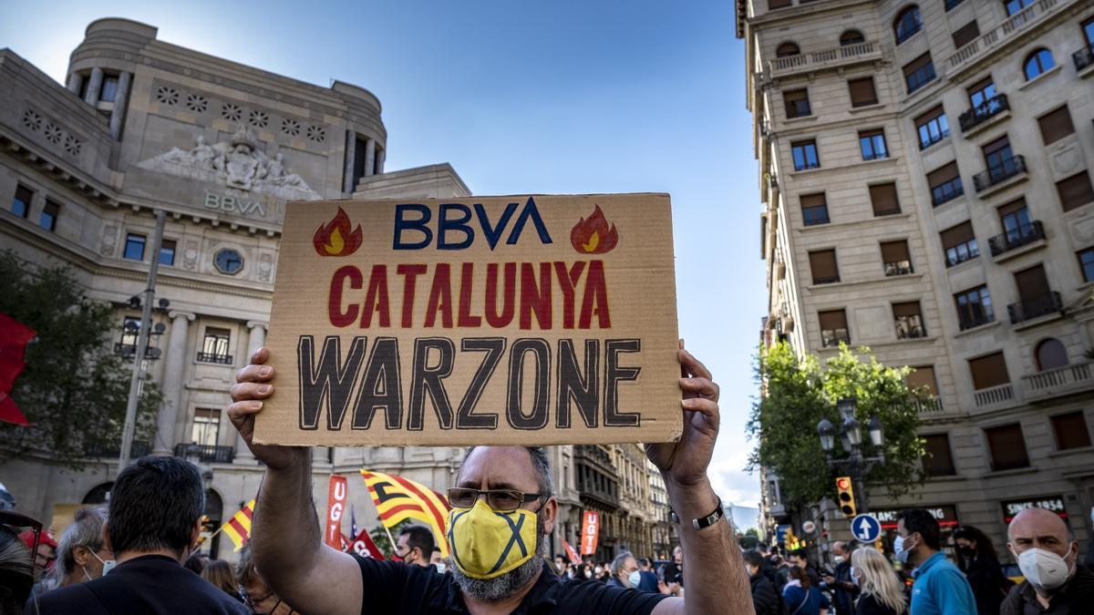 Un protestant sosté una pancarta a Barcelona durant les mobilitzacions contra l'ERO de BBVA el 10 de maig de 2021. Foto: Paco Freire/SOPA Images via ZUMA Wire/dpa