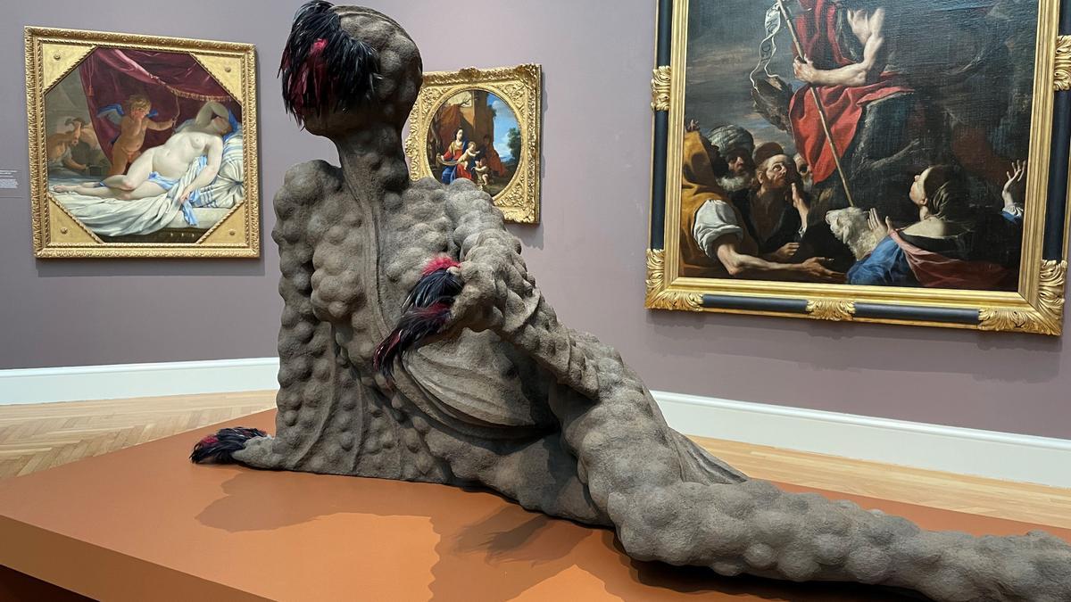Vista de la obra 'Outstrecthed', donde aparece una mujer acostada con la piel llena de protuberancias