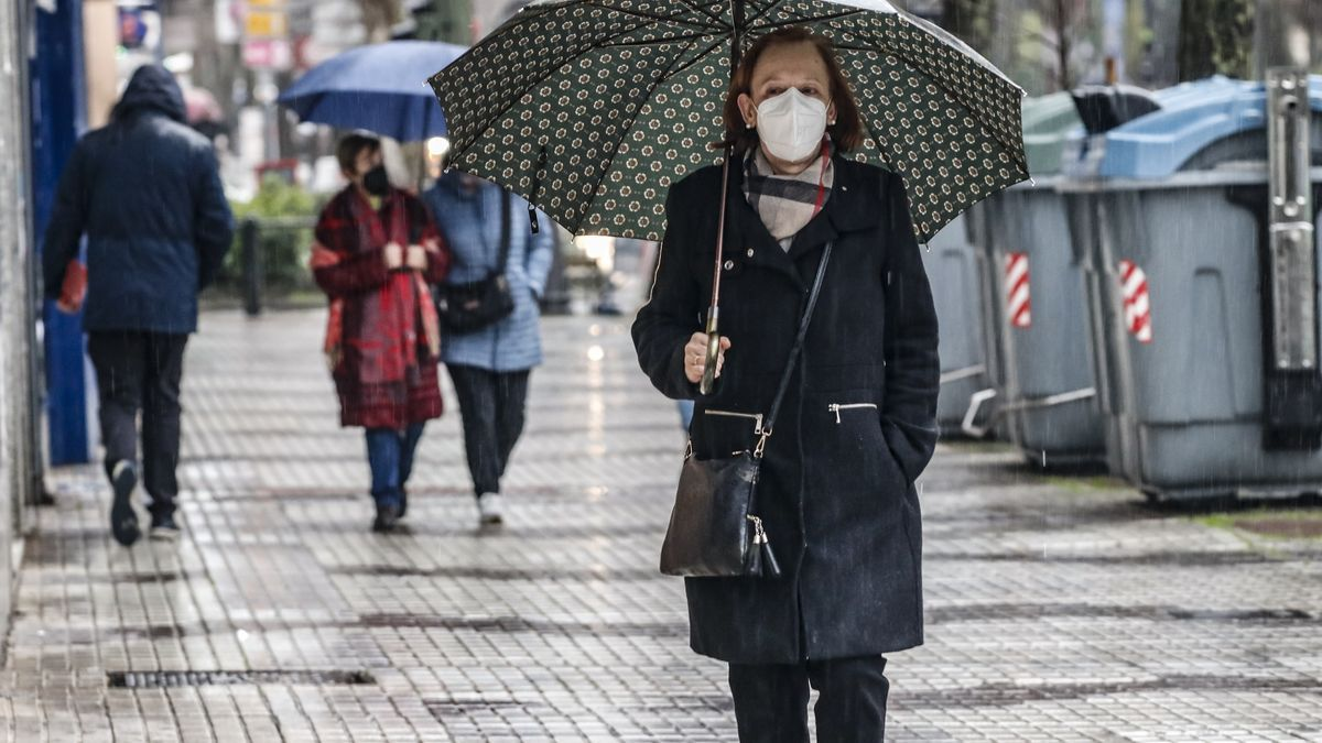 Una mujer pasea bajo la lluvia.