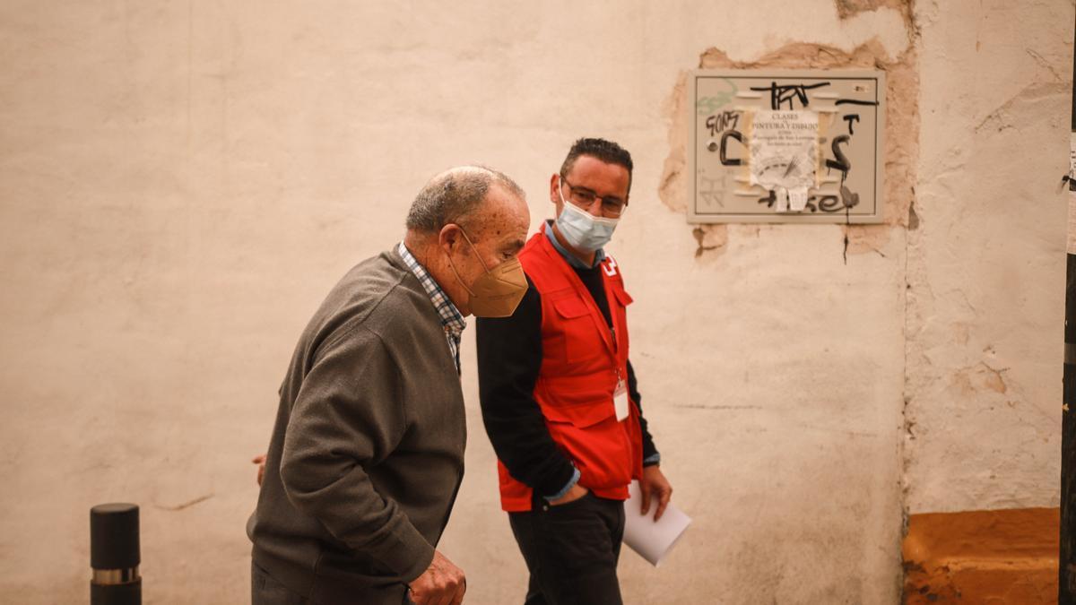 Un voluntario de Cruz Roja acompaña a un mayor a vacunarse.