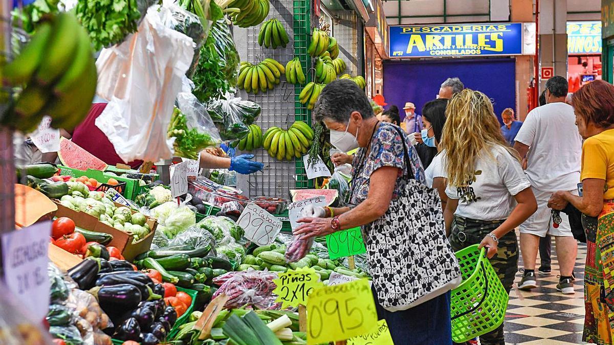 Clientes en un puesto de fruta y verduras en el Mercado Central. | |