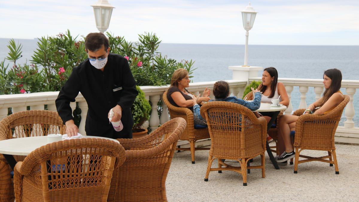 Cambrer desinfectant el mobiliari de la terrassa de l'Hotel Costa Brava.