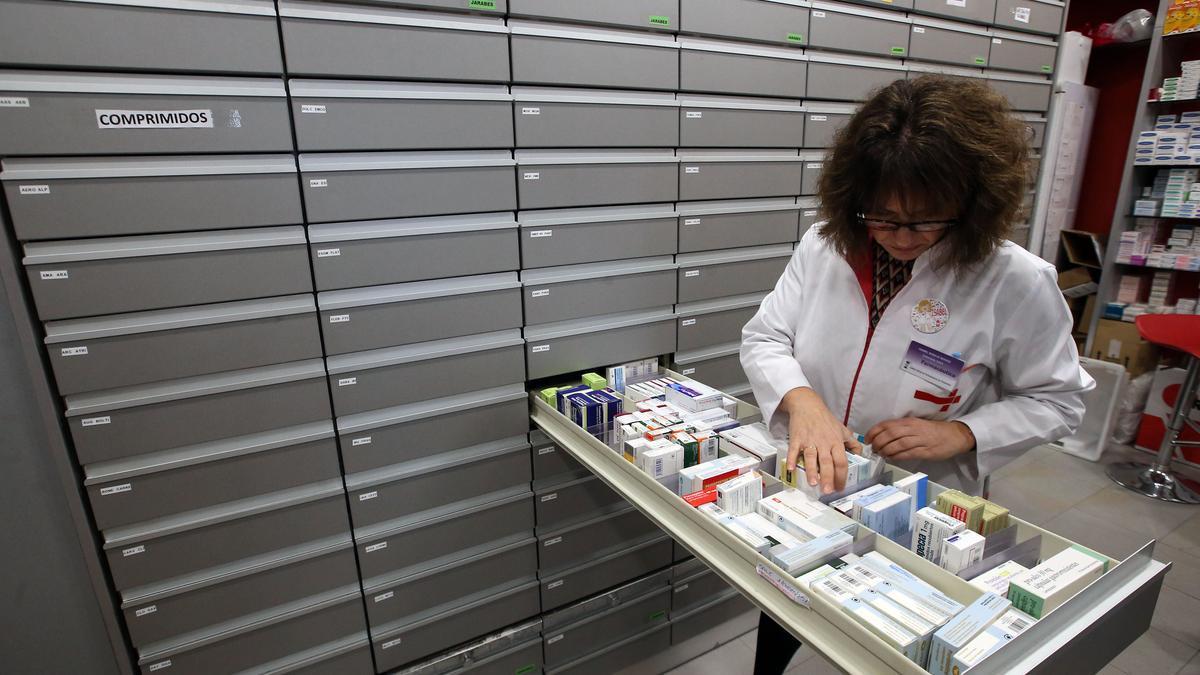 Una farmacéutica busca una medicamento en uno de los armarios de una farmacia.