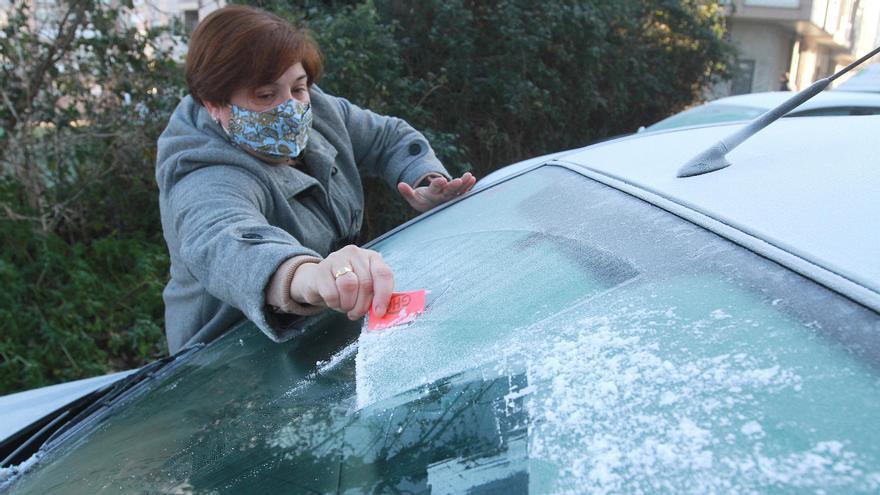 Una mujer retira el hielo del parabrisas de su vehículo, hoy en Ourense, la provincia más helada.
