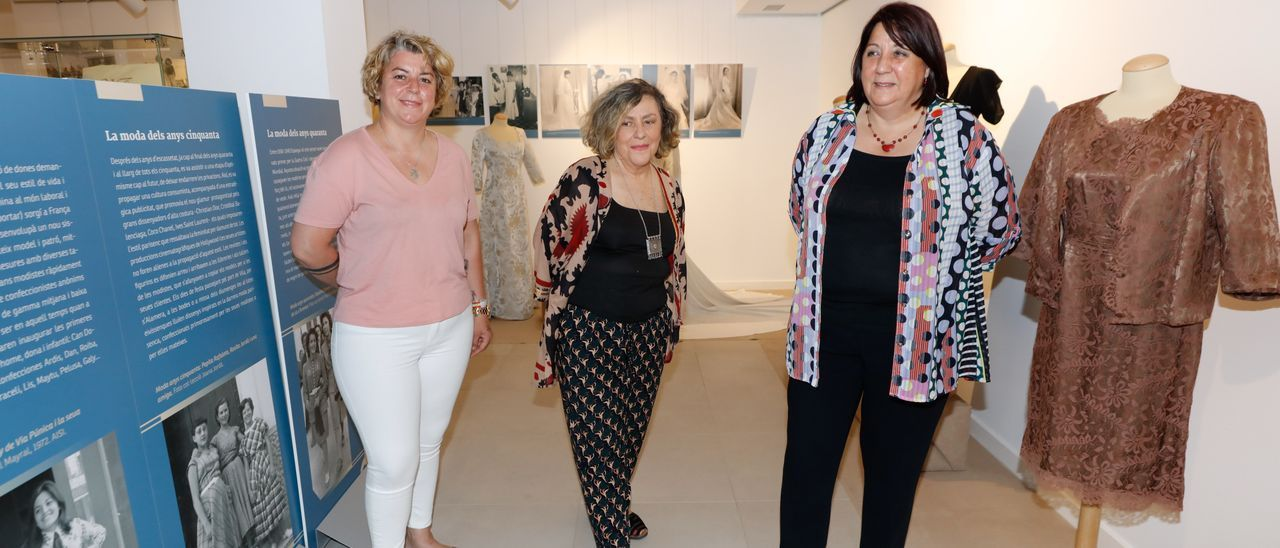 Margarita Ferrer Fuster, Neus Escandell y Lina Sansano posan junto a un diseño de Margarita Fuster Bonet, en la exposición 'Moda en Ibiza: coser y vestir'