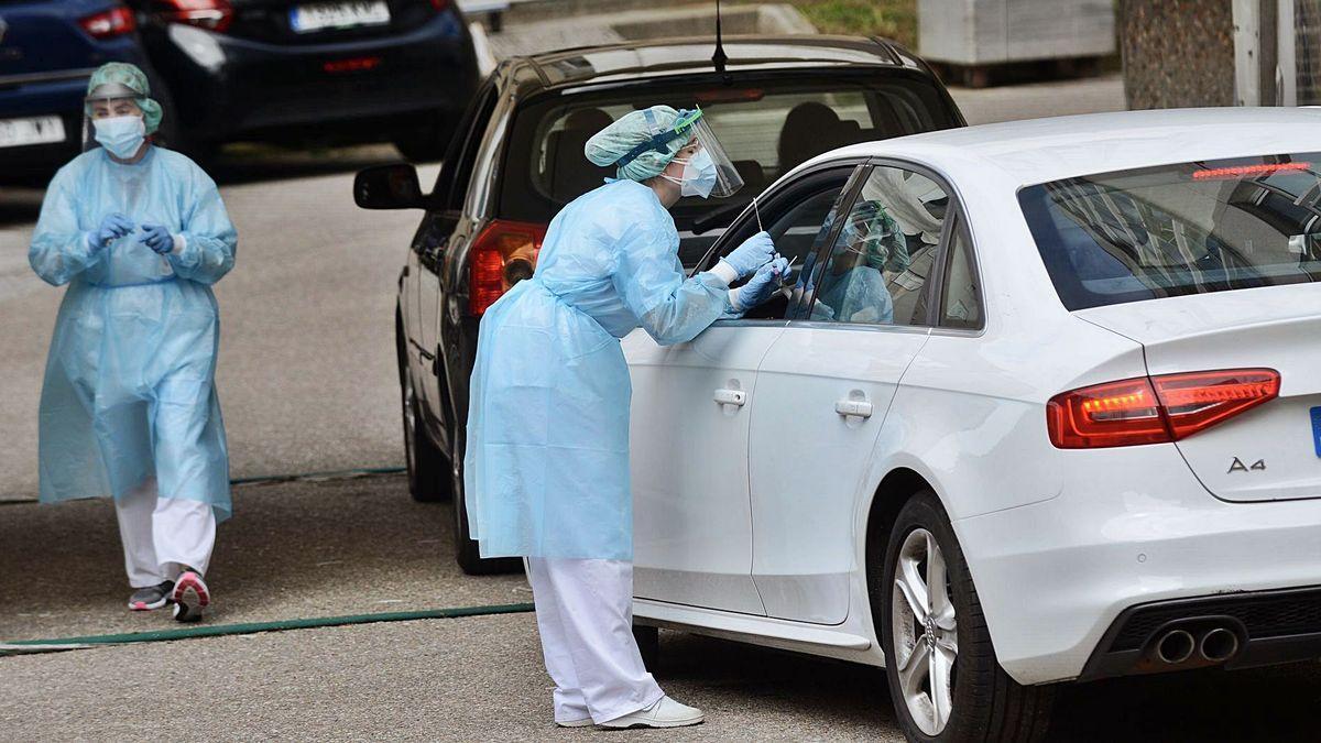 """Dos sanitarias realizando pruebas PCR en el espacio """"COVID-auto"""" del Provincial."""