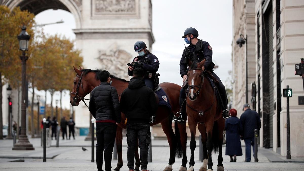 Agentes a caballos por los Campos Elíseos de París.