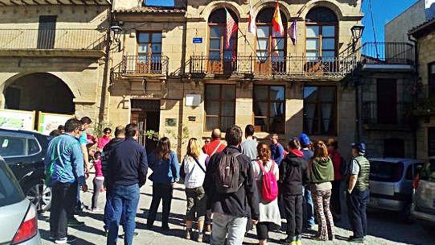 Un grupo de turistas repara el pasado fin de semana en el reloj y en la fachada del Ayuntamiento Fermoselle.