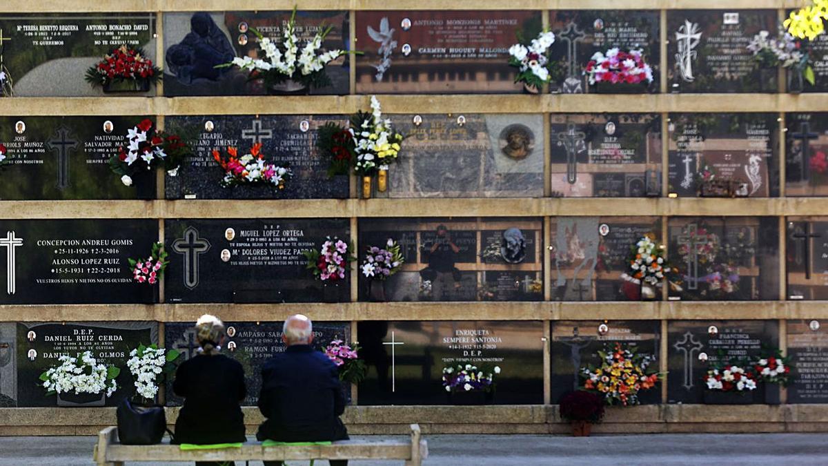 Dos personas recuerdan a sus seres queridos en el cementerio general de València.  | EDUARDO RIPOLL