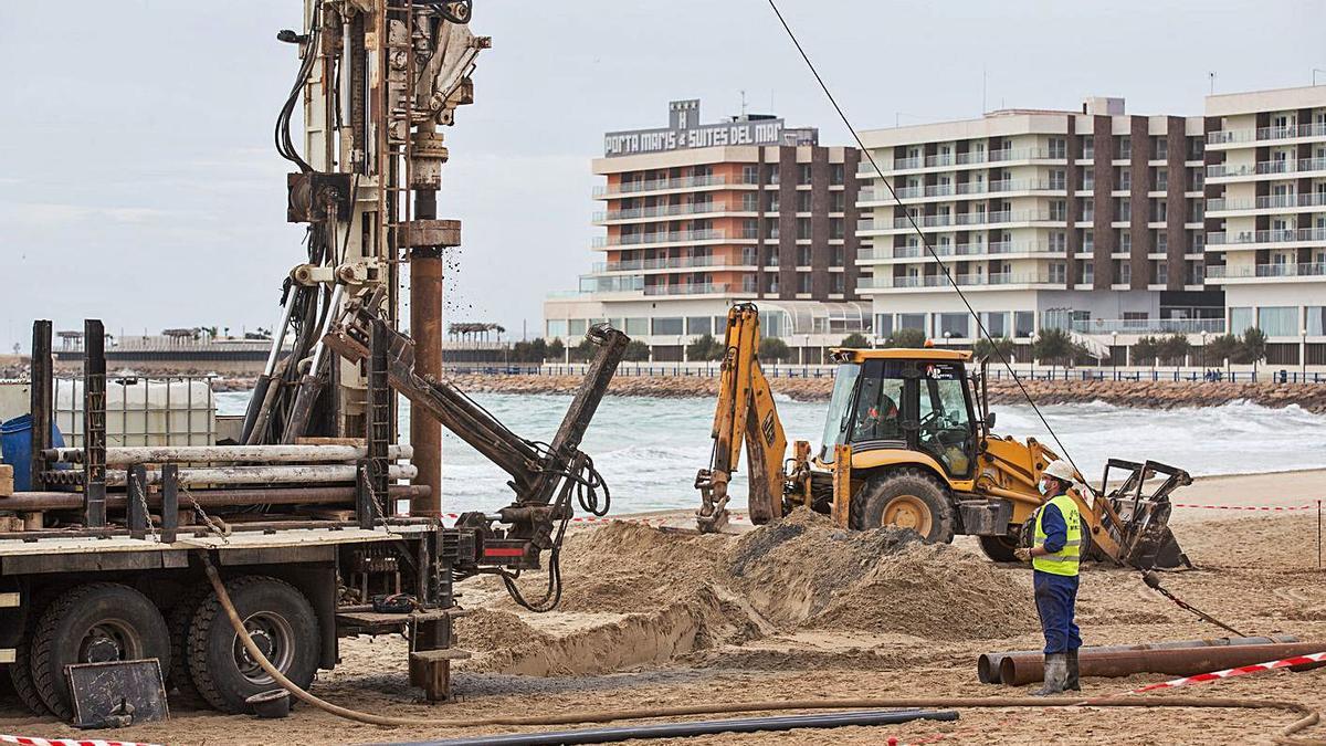 Maquinaria trabajando sobre la arena de la playa del Postiguet, esta semana.  |