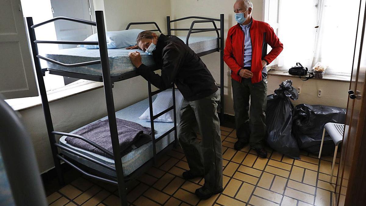 Los peregrinos Miguel Ángel Alonso, a la izquierda, y Javier López, en su habitación del albergue. | Luisma Murias