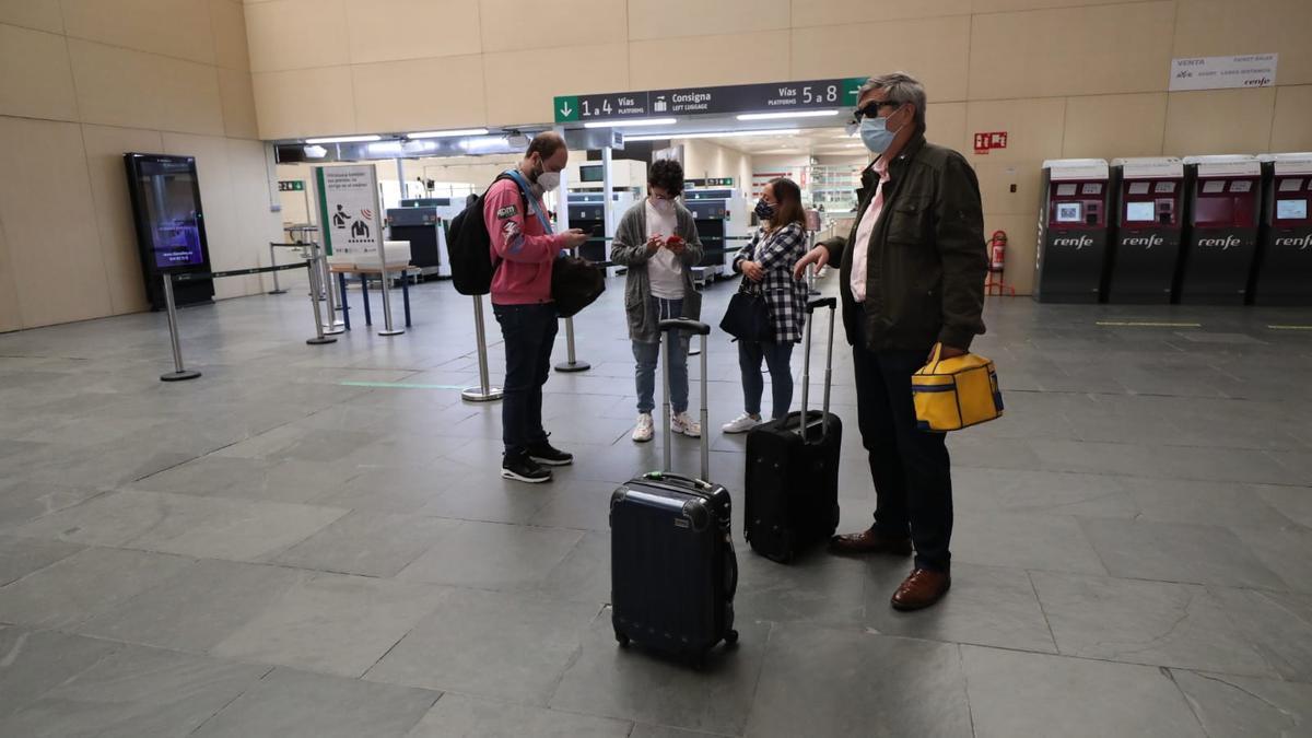 Algunos pasajeros del tren afectado por la avería de Ouigo, esperan la llegada en los accesos a las vías de la estación de Delicias.