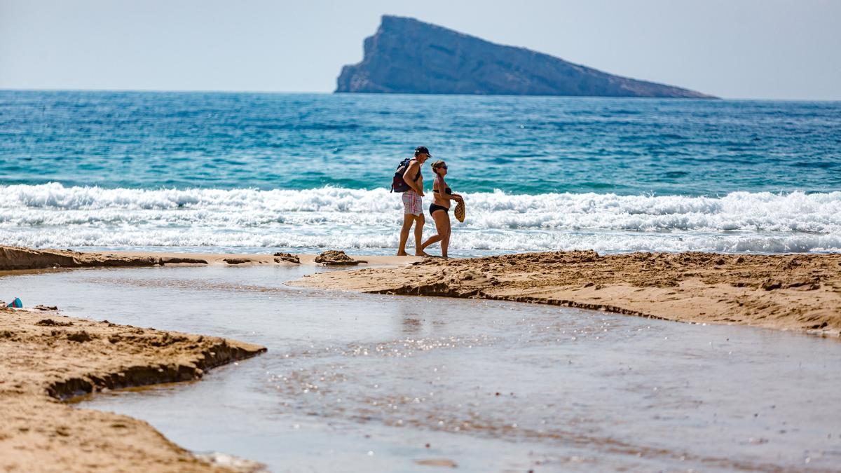 Una pareja de turistas pasea por la playa de Levante de Benidorm, vacía de turistas este invierno