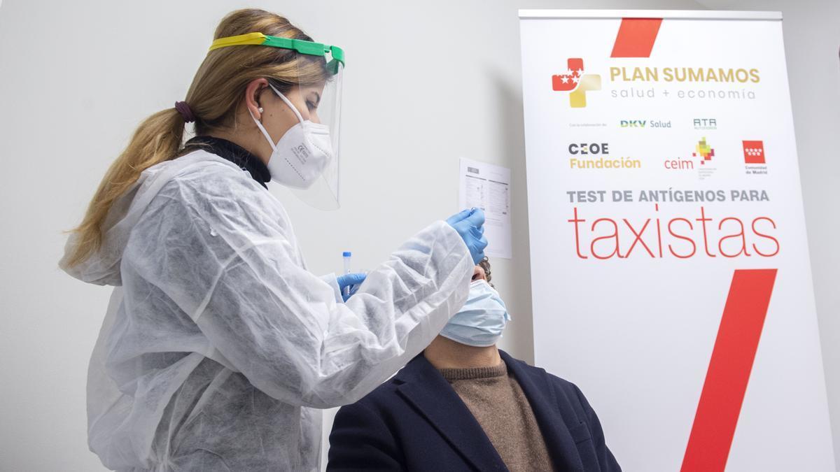 Una trabajadora sanitaria realiza un test de antígenos a un taxista de la Comunidad de Madrid