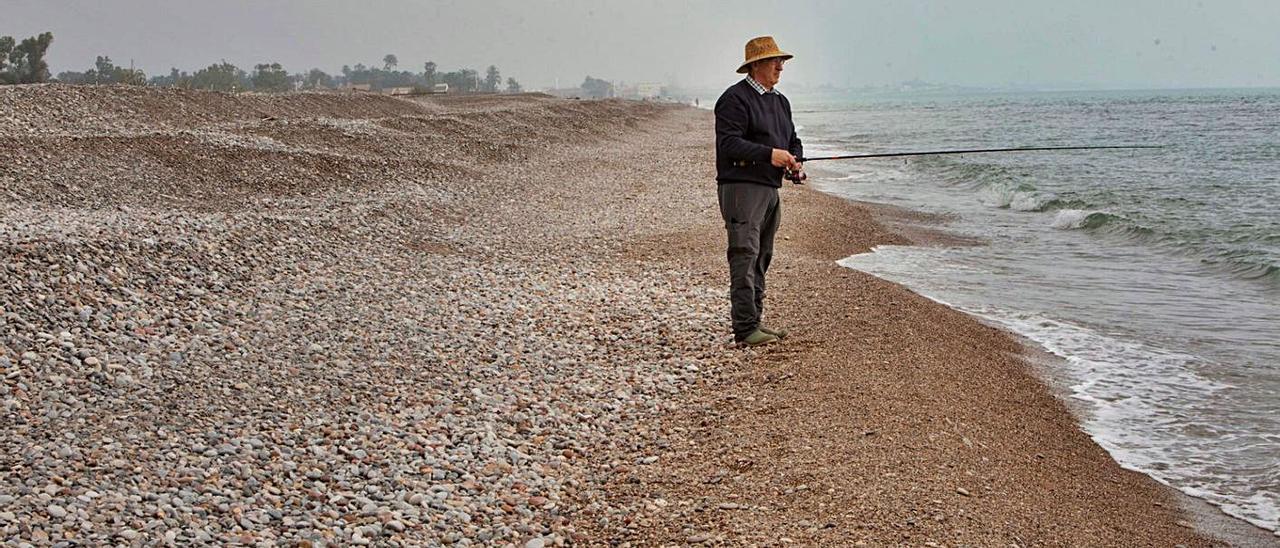 Un pescador, ayer, en una de las playas al norte de Sagunt, con escalones de grava. | DANIEL TORTAJADA