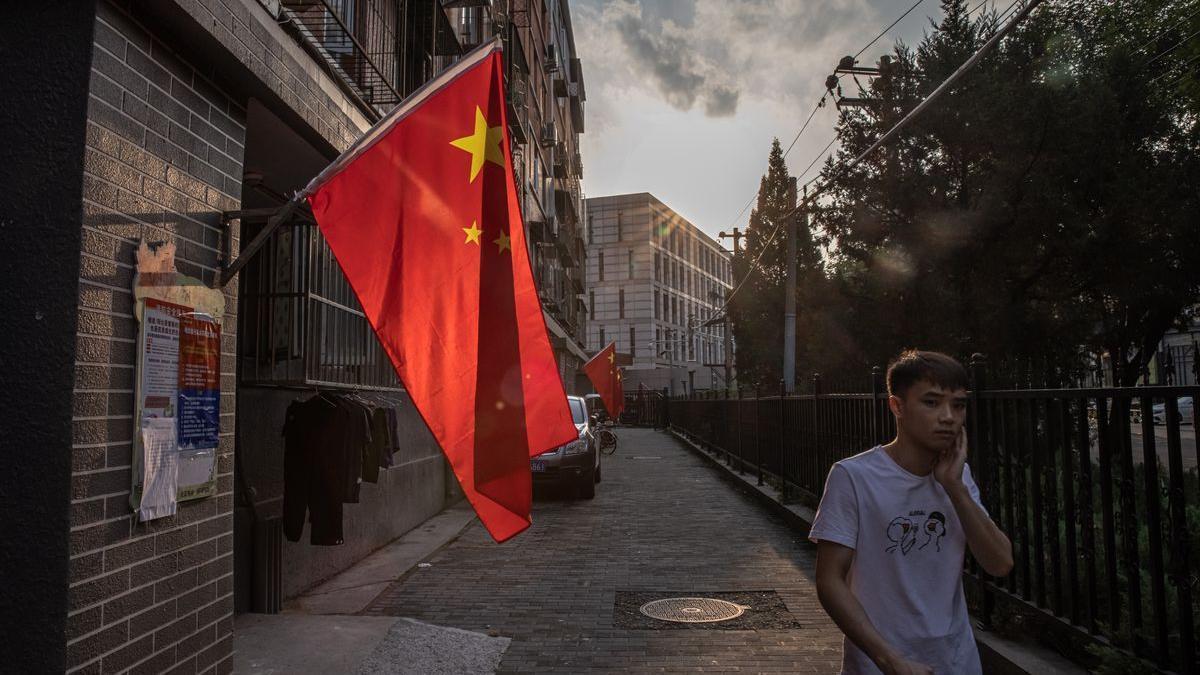 Un hombre camina junto a un edificio residencial, en los días previos a la celebración del Día Nacional de China.