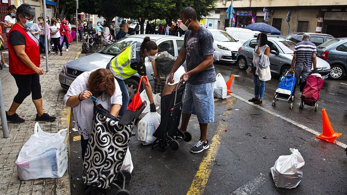 Las colas del hambre, con varias personas que recogen alimentos en la sede de la Despensa Solidaria en Alicante.