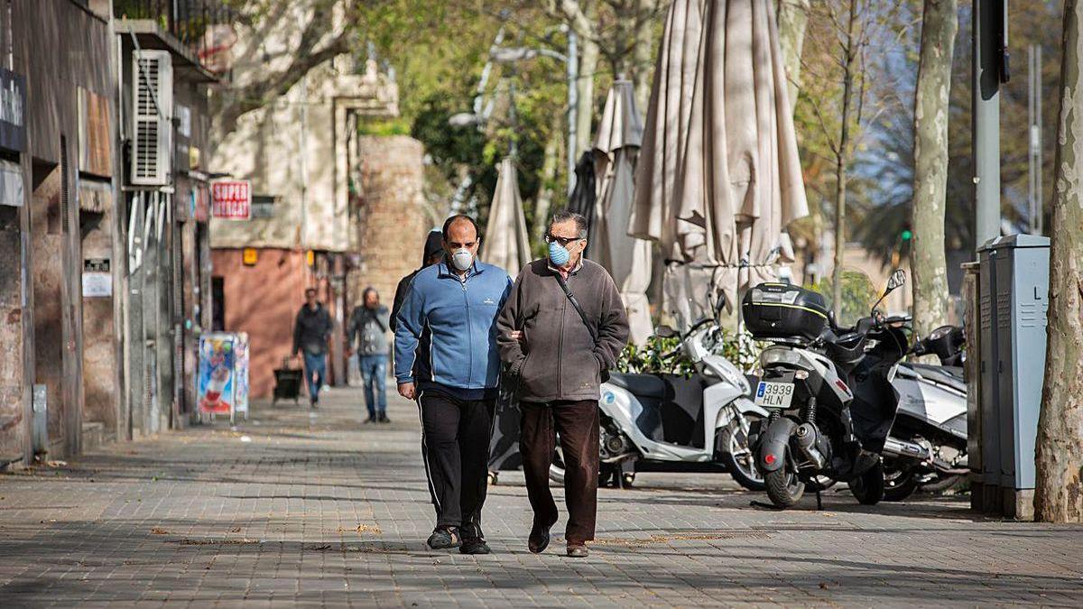 Dos hombres caminan con mascarilla por Barcelona.