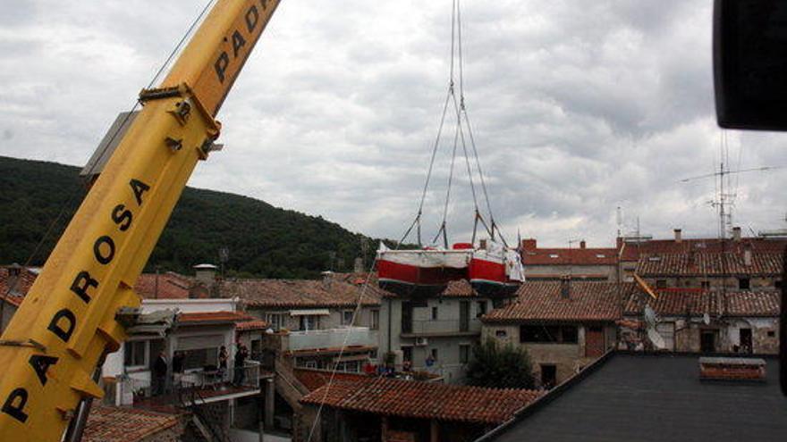 Una grua treu el catamarà d'en Pepe a Castellfollit abans d'anar cap a Roses