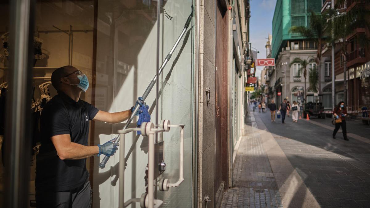 Un trabajador limpia un escaparate en Santa Cruz.