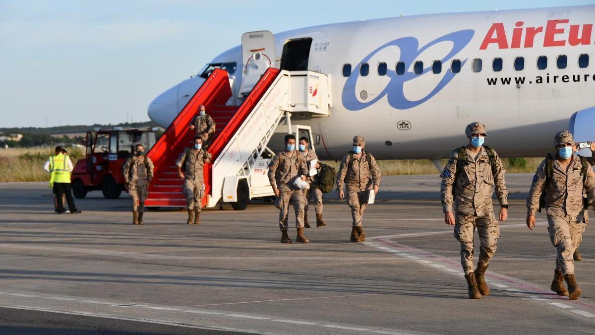 Varios militares de la Brigada Extremadura XI se bajan del avión.