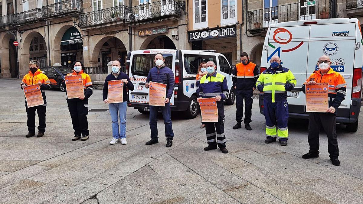 El alcalde, Pérez Jácome, con miembros de Protección Civil en la Praza Maior. |   // FDV