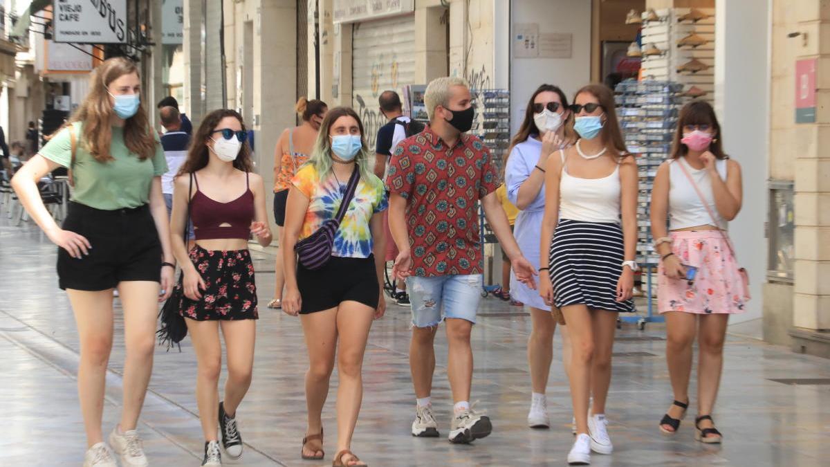 Un grupo de personas pasea por una calle de Cartagena con la mascarilla puesta.