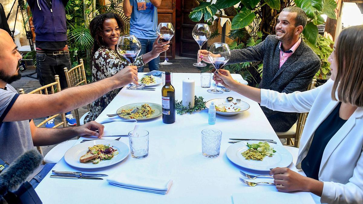 Cuatro participantes de la Escuela de Actores de Canarias brindan sin chocar las copas durante el simulacro de almuerzo en el restaurante Casa Montesdeoca.     JUAN CASTRO