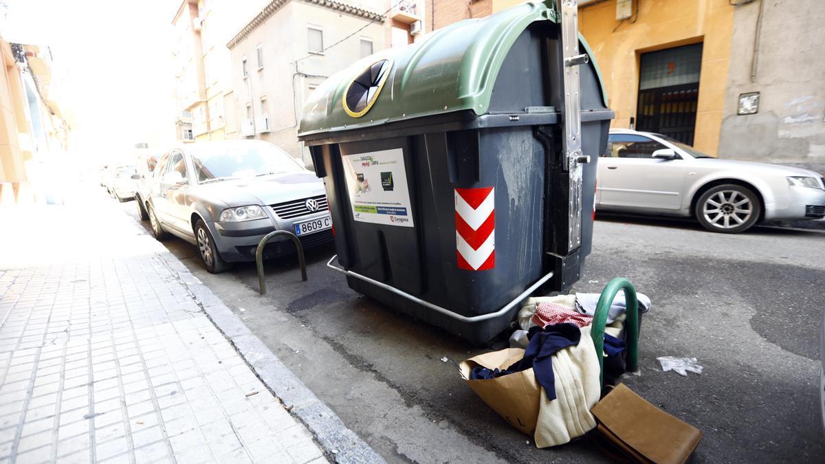 Un contenedor con basura en su exterior en una calle de Zaragoza.
