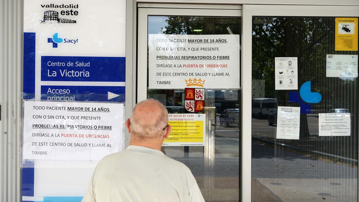 Un hombre frente a la puerta de un centro de salud.