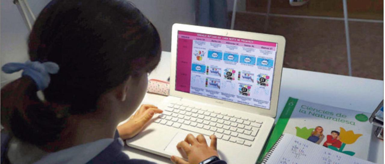 Una alumna consulta su ordenador durante el confinamiento, para seguir con su aprendizaje desde casa.