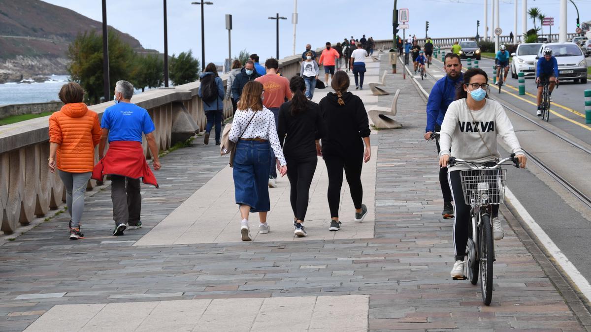 Gente paseando en el paseo marítimo coruñés.