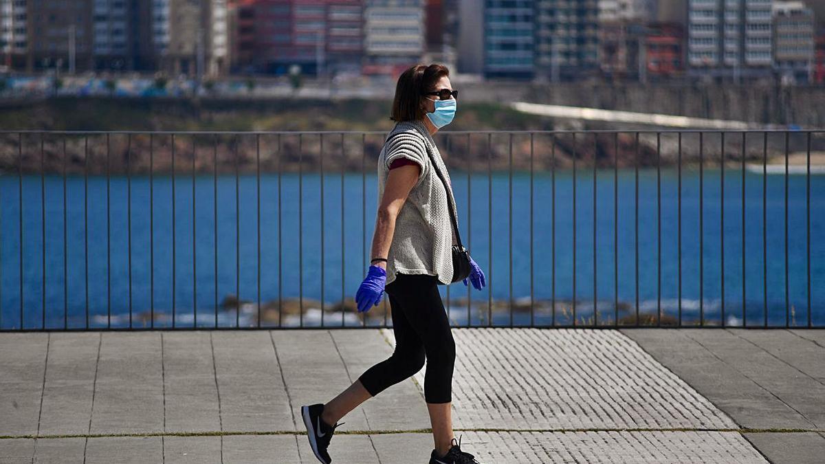 Una mujer, paseando por la ciudad de A Coruña con mascarilla y guantes. |   // CARLOS PARDELLAS
