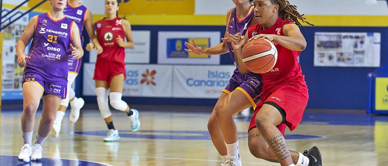 Maya Caldwell, escolta del SPAR Gran Canaria,  se interna en la zona ante la defensa de Irene San Román, del Clarinos. | | J. DE HARO