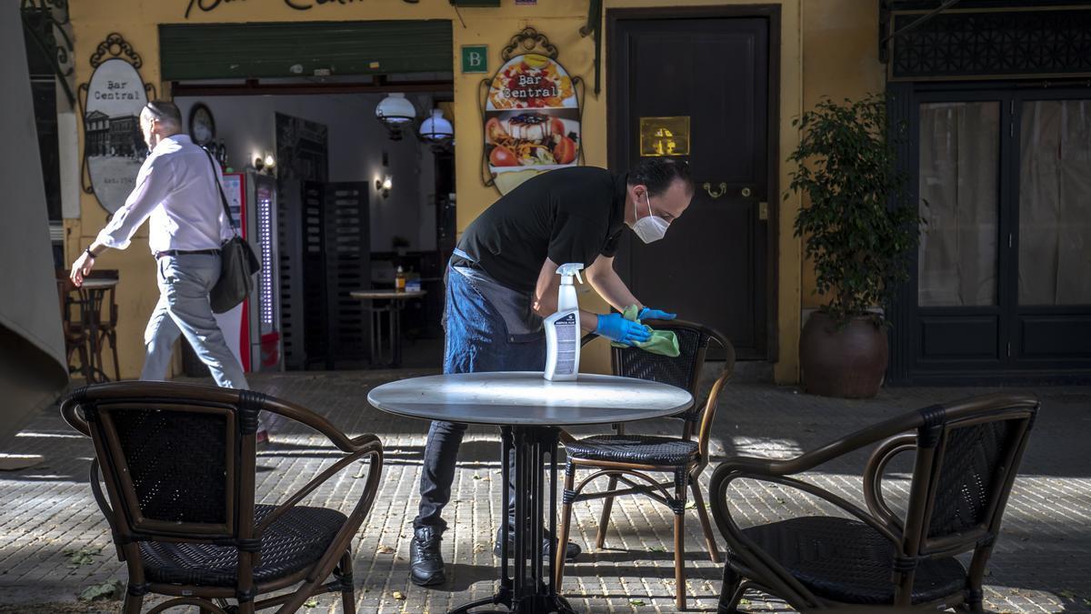 Un restaurador desinfecta las sillas de su terraza en Palma
