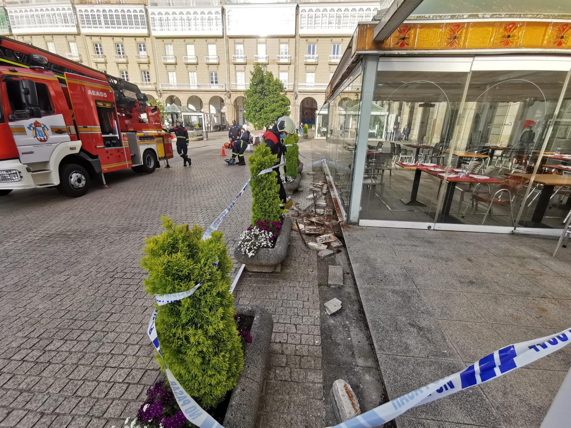 Los bomberos acuden a la plaza de María Pita a reparar el friso decorativo de la terraza de la pizzería Cambalache
